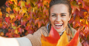 woman very happy smiling at selfie with fall leaves behind her