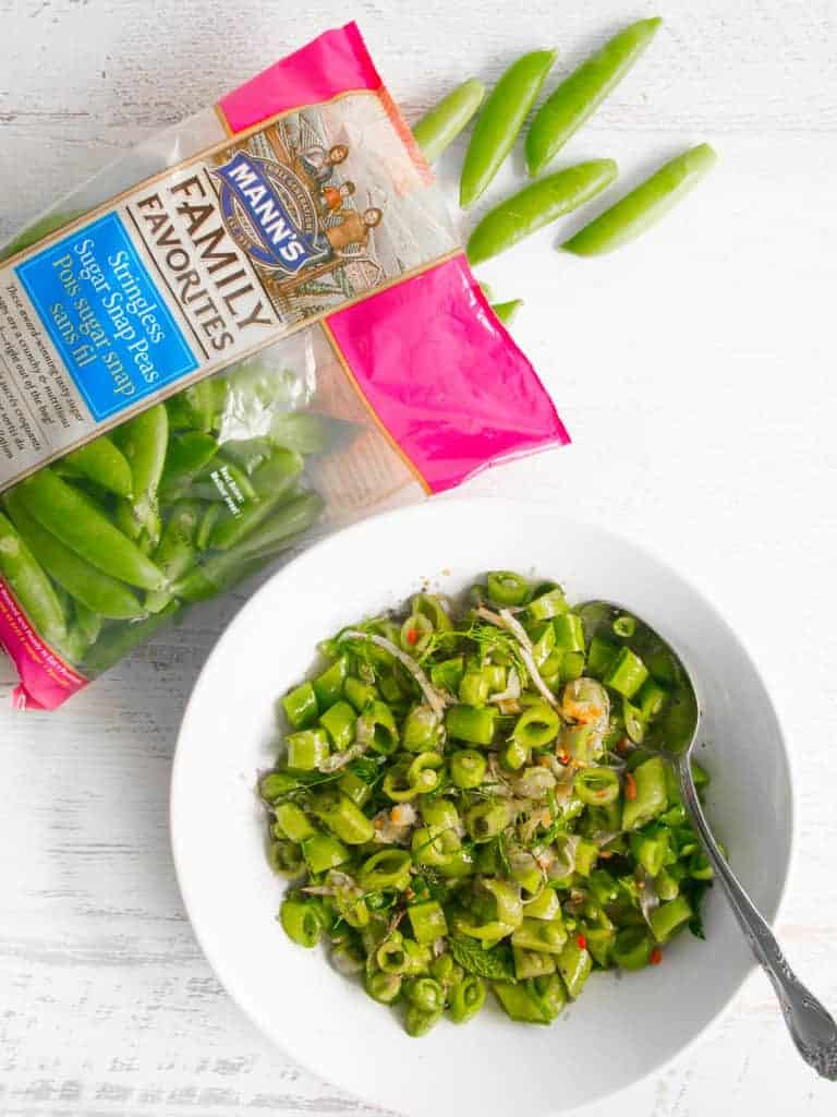 bag of sugar snap peas with chopped snap peas in salad bowl
