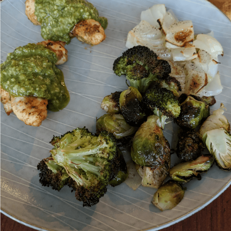 dinner plate with air fried chicken tenders with basil pesto, roasted broccoli, onions and brussels sprouts all part of low carb day in carb cycling for weight loss meal plan