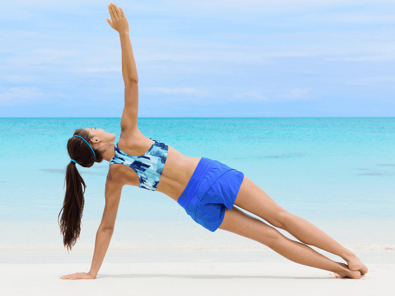 woman on beach doing side arm plank