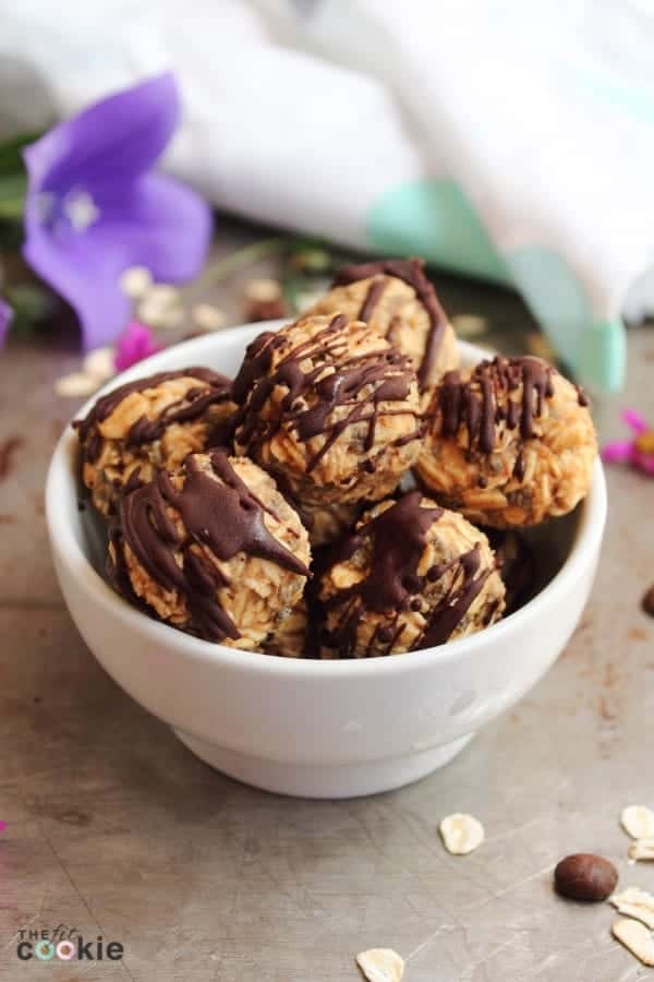energy balls in a white bowl with chocolate drizzled on top